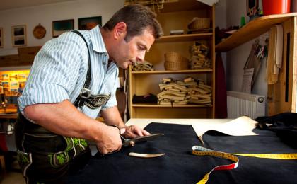 Engelbert Aigner senior schneidet das Hirschlder für eine Lederhose zu