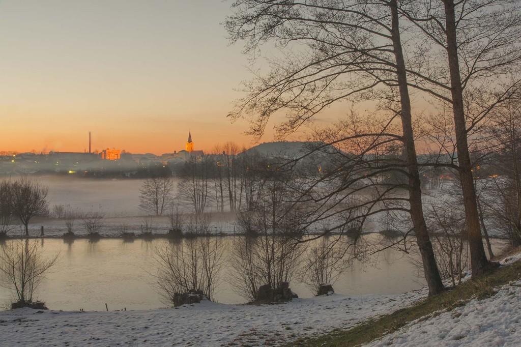 Sonnenuntergang über Teisendorf im Winter mit der Kirche St. Andreas und dem Pfarrer-Weiher im Vordergrund (c) roha-fotothek Fürmann