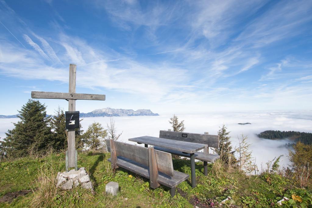 das Gipfelkreuz auf den Ahornbüchsenkopf oberhalb der Rossfeldhoehenringstrasse (Rossfelstrasse) mit dem Untersberg im Hintergund - Berchtesgaden