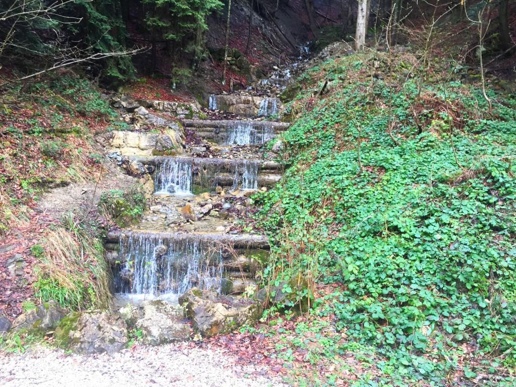 Kleiner Wasserfall an Wegkreuzung