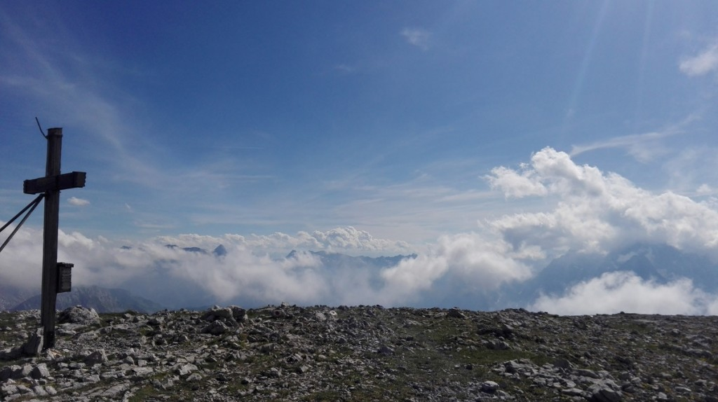 Das Gipfelkreuz am Hohen Brett beobachtet die Wolkenspiele über den Berchtesgadener Alpen