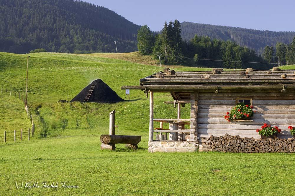 die Hütte der Köhler in Neukirchen in der Gemeinde Teisendorf mit dem Kohlenmeiler im Hintergrund, Berchtesgadener Land, Oberbayern, Deutschland