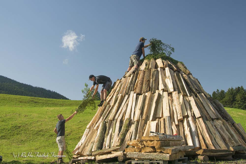 die Köhler in Neukirchen in der Gemeinde Teisendorf bei der Arbeit, Berchtesgadener Land, Oberbayern, Deutschland sie decken den Meiler oben mit Fichtenreisig ab