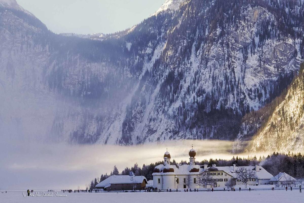 der zugefrorenen Königsee, tiefverschneit, mit St. Bartholomä im Hintergrund in der Morgensonne, ein sehr seltenes Naturschauspiel im Berchtesgadenre Land, Bayern