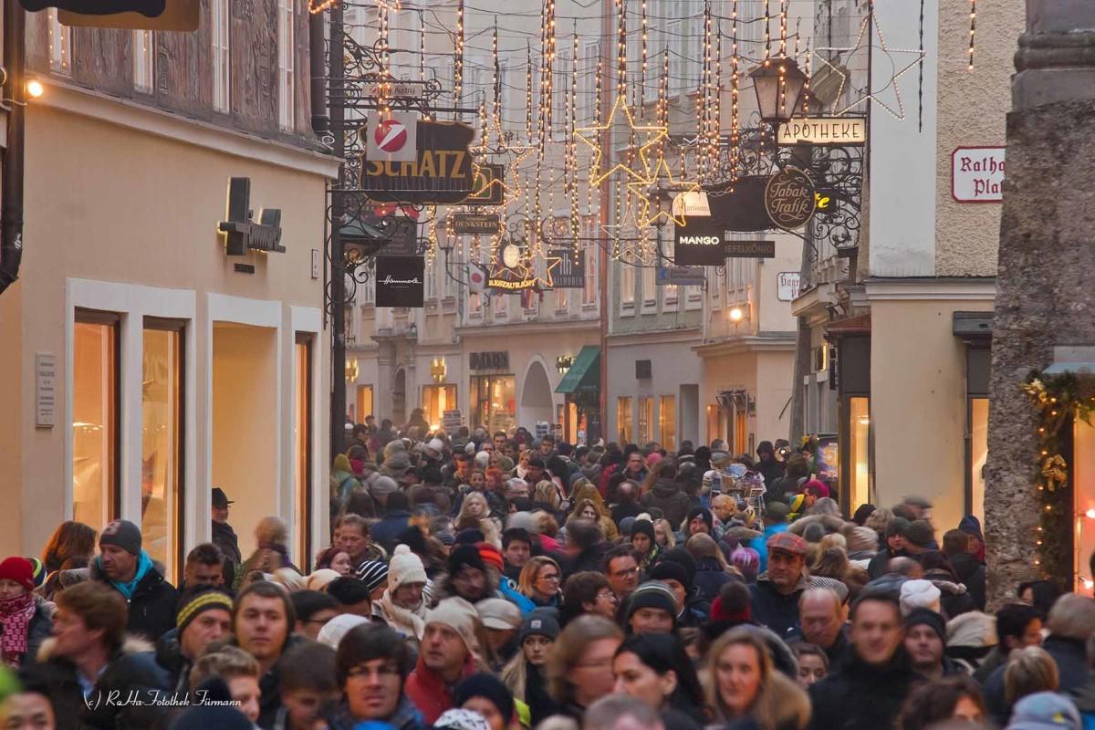 die Getreidegasse in Salzburg mit den vielen charaktersistischen Zunftzeichen an den Fassaden im vorweihnachtlichen Schmuck