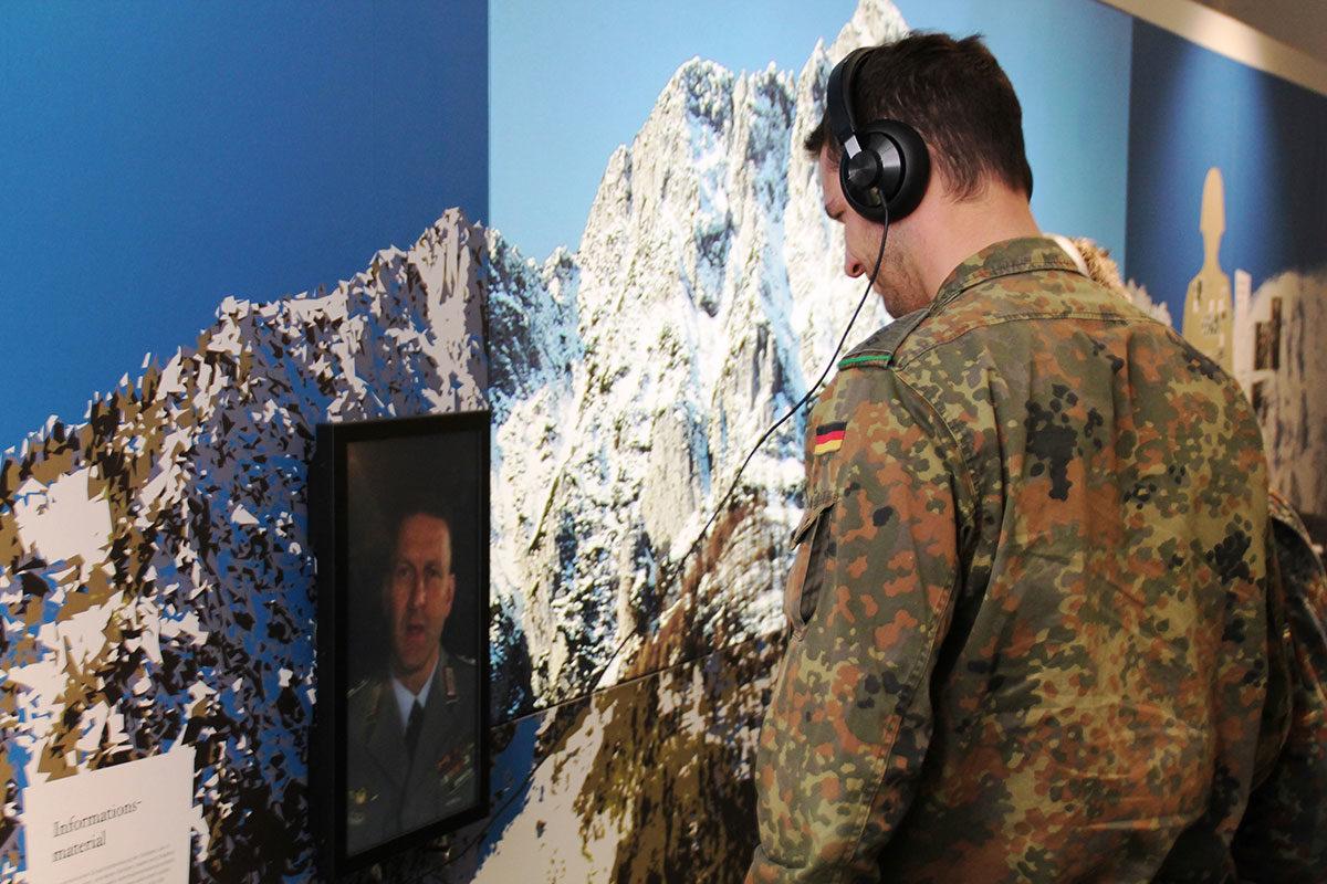 Ein Soldat der Gebirgsjägerbrigade hört sich einen Interviewbeitrag vor der Fotokulisse des Hochstaufens an
