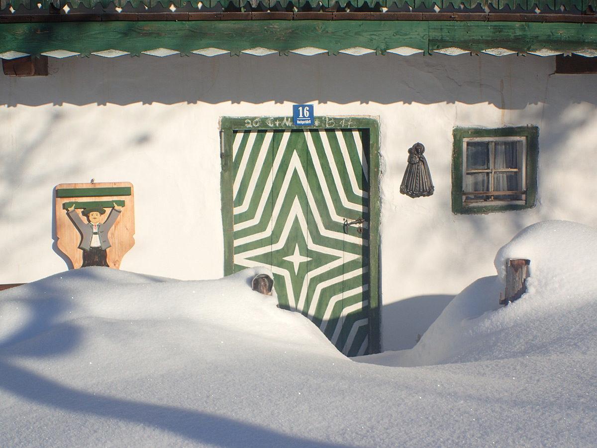 Halb im Schnee versunken ist die wunderschöne Eingangstür vom Unterhochgartlehen. Die typische alte Berchtesgadener Tür ist noch original von 1680