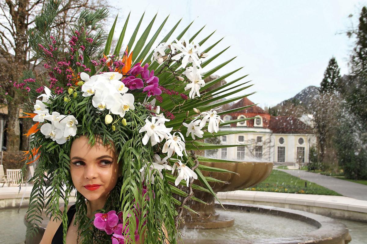 Florale Pracht auf dem Kopf platziert. Model Jessika vor dem Alpensolebrunnen des Königlichen Kurgartens Bad Reichenhall, dahinter die Konzertrotunde © Fischer/alpgold
